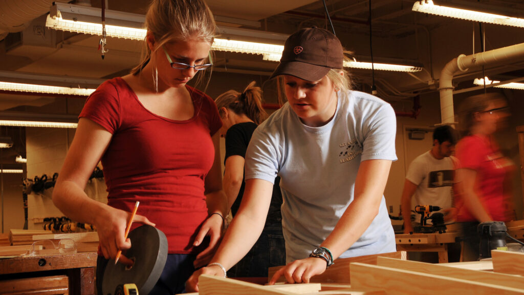 Two female students working on building an object in the NC State Crafts Center wood shop.